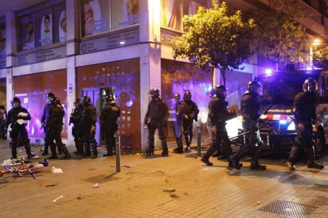 Un grupo de Mossos toma posiciones delante del banco desalojado para...
