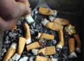 Un hombre apaga un cigarrillo.