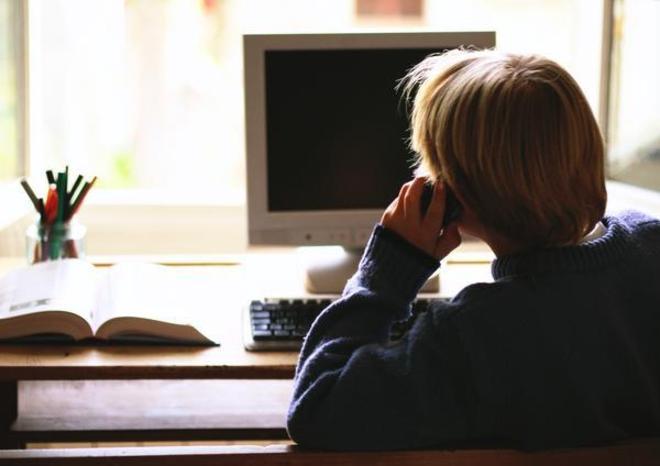 Un niño solo en su habitación habla por teléfono.
