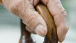 La mano de una persona mayor apoyándose en su bastón