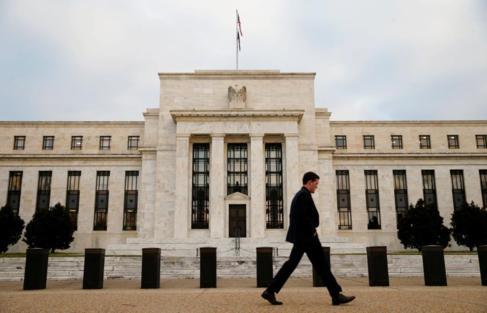 Un hombre caminando delante del banco de la Reserva Federal de...