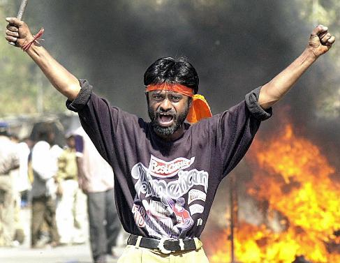 Un hombre con una barra de hierro ante los incendios en la matanza de...