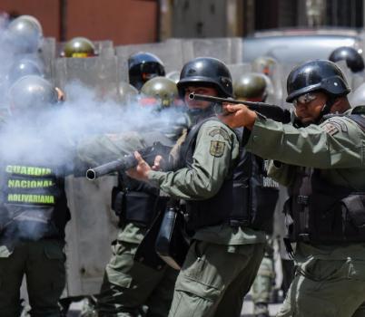 Policías apuntan a los manifestantes que piden comida y que se...