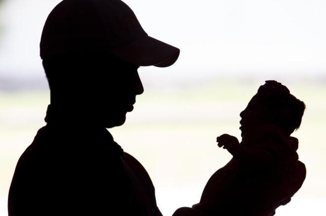 Un padre sosteniendo a su hija con microcefalia.