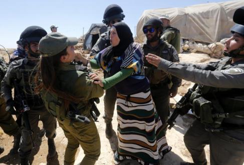 Una soldado se enfrenta con una mujer palestina durante la demolición...