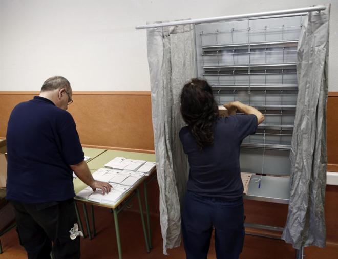 Dos operarios colocan las papeletas del 26-J en un colegio electoral...
