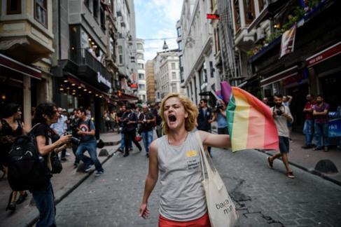 Una mujer, con la bandera arcoiris, se enfrenta a la policía en la...