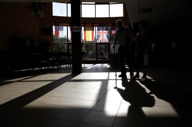 Una pareja de ancianos acude ayer por la mañana a votar a un colegio...