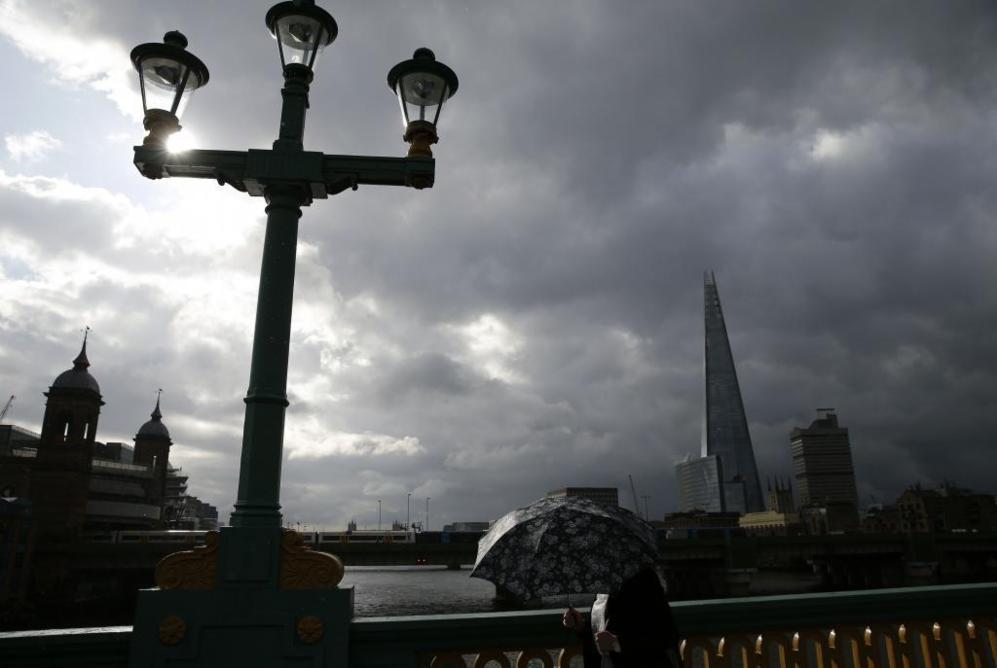 Una viandante transita bajo su paraguas por el puente de Southwark...