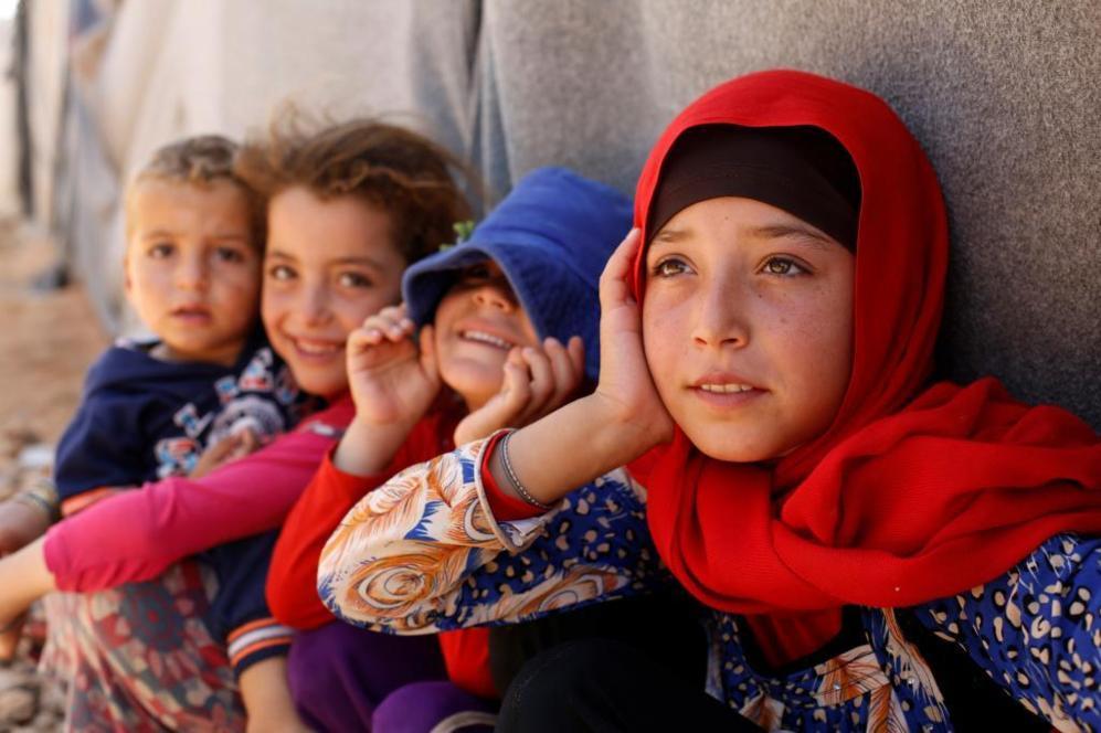 Niños refugiados sirios posan frente al fotógrafo en el campo de...