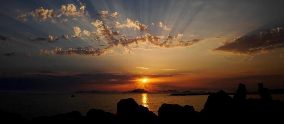 Gente disfrutando de la puesta de sol frente al mar en Marsella,...