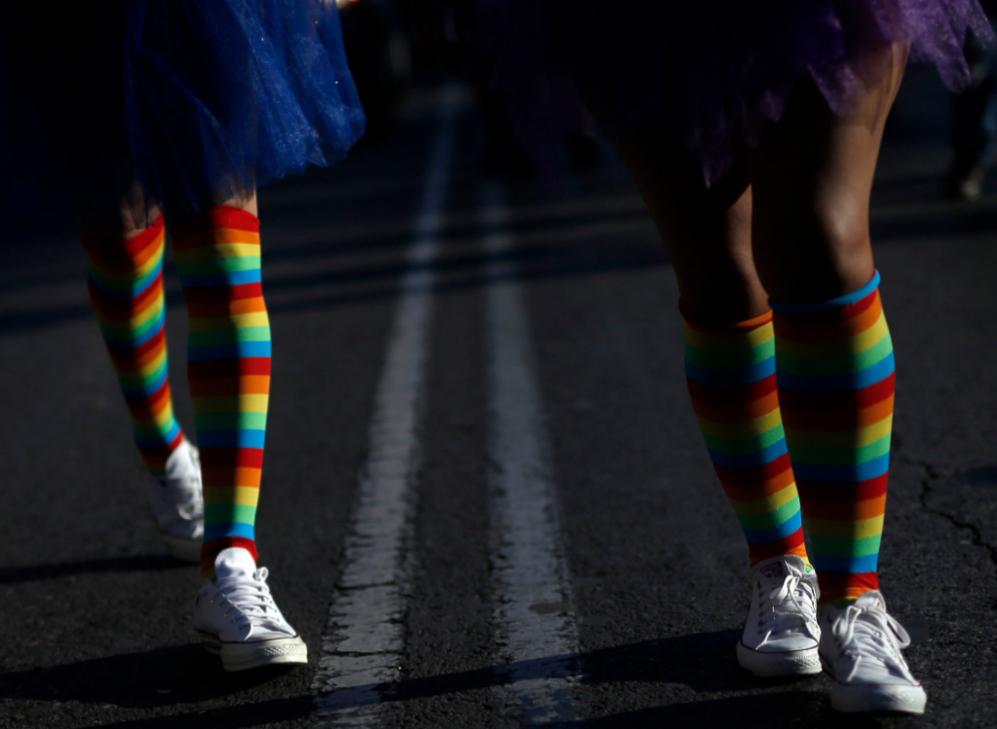 Dos asistentes al Orgullo caminan con los colores de la bandera...