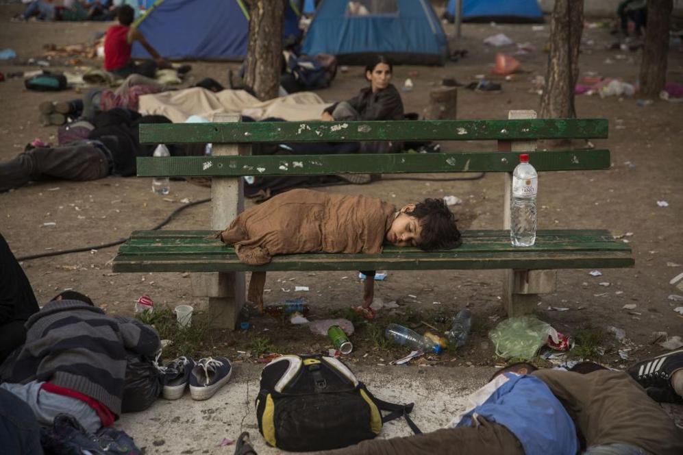 n niño durmiendo al amanecer en un banco de la plaza Bristol de...