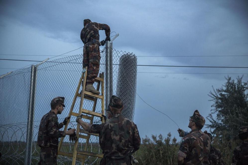 Soldados húngaros terminando de instalar la alambrada fronteriza...