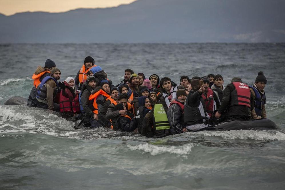 Decenas de refugiados llegando en un bote hinchable lleno de agua, a...