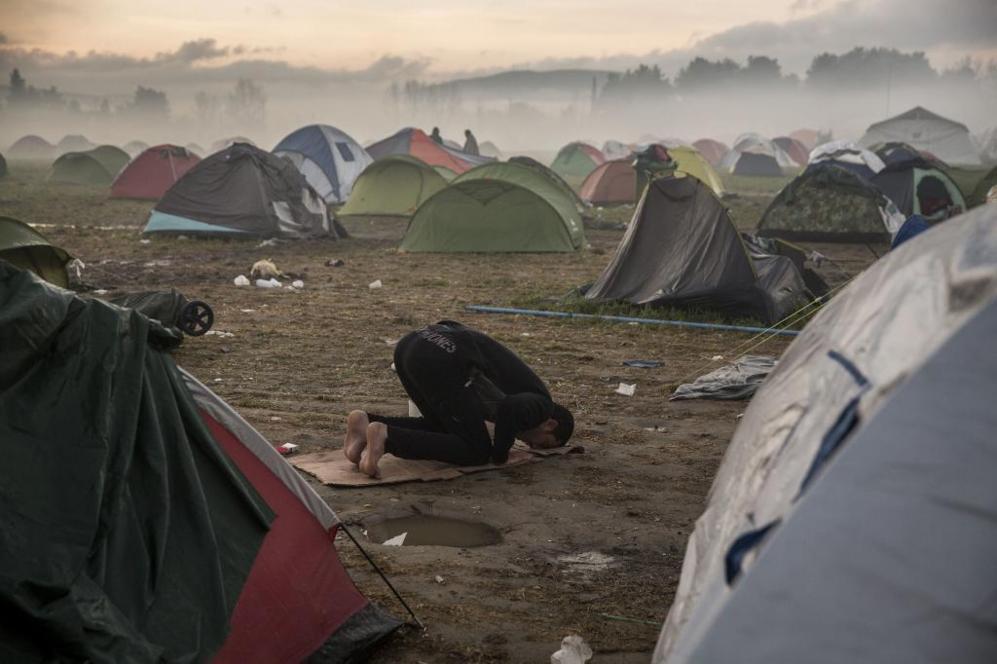 Un refugiado rezando al amanecer en el campo de refugiados de Idomeni,...