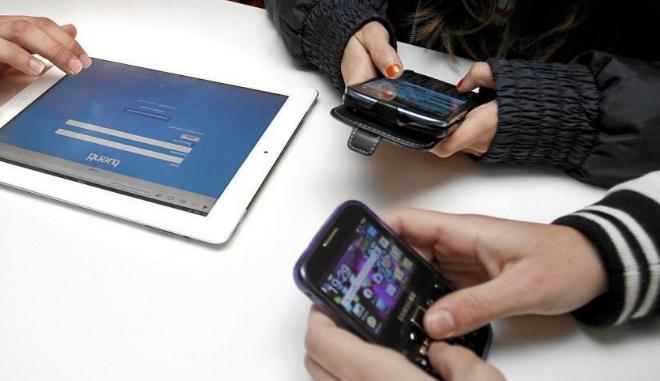 Jóvenes utilizando tablets y smartphones.
