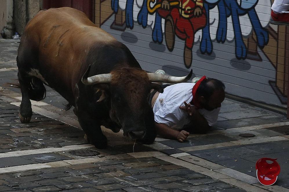 Un corredor, herido en el suelo al lado de uno de los toros en la...