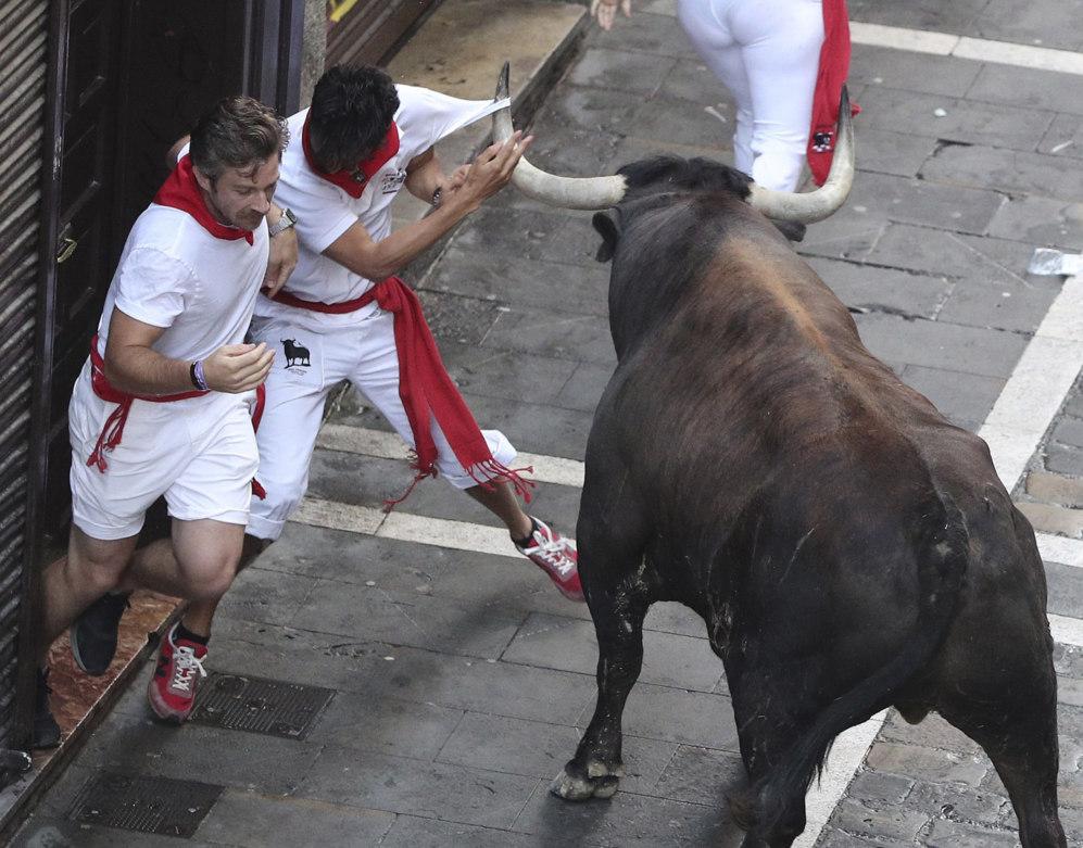 Un toro desgarra la camiseta de uno de los corredores