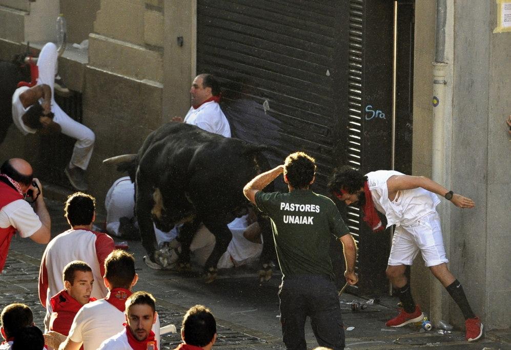 Al fondo, un mozo cuelga del asta derecha de uno de los toros