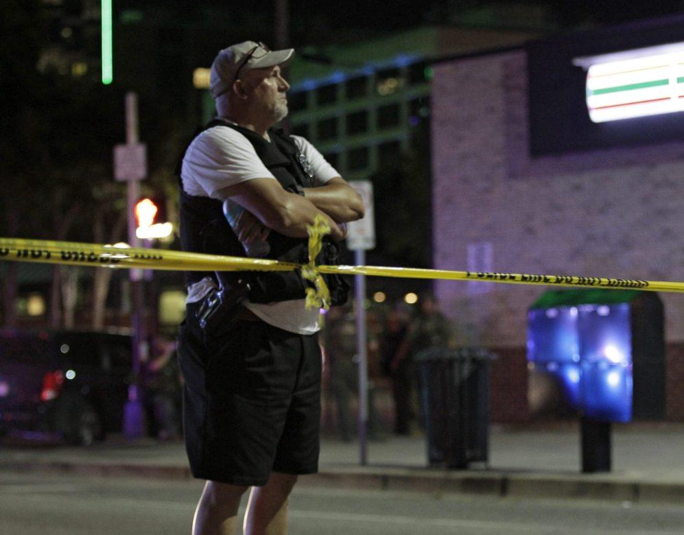 Un agente de policía observa tras el cordón policial el escenario...