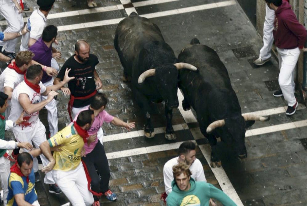 Dos mozos corren delante de los toros en la cuesta de Santo Domingo