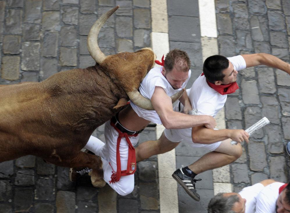 Uno de los toros embiste a dos corredores en el tramo del Ayuntamiento