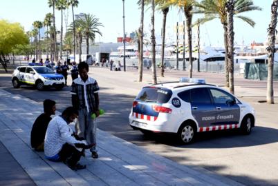 Manteros frente a un coche de los Mossos esta mañana en Barcelona.