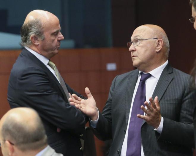 El ministro de Economía en funciones, Luis de Guindos, con su...