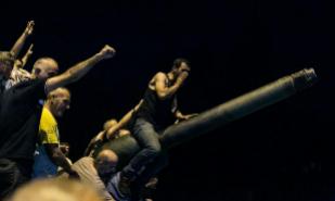 Un grupo de hombres toman un tanque cerca del puente de Fatih Sultan...
