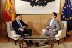 Mariano Rajoy y Albert Rivera se abrochan sus chaquetas durante su...
