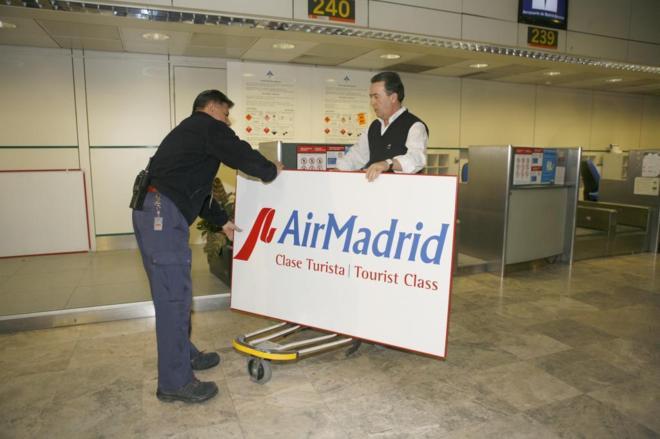 Trabajadores del aeropuerto de Barajas trasladan un cartel de Air...