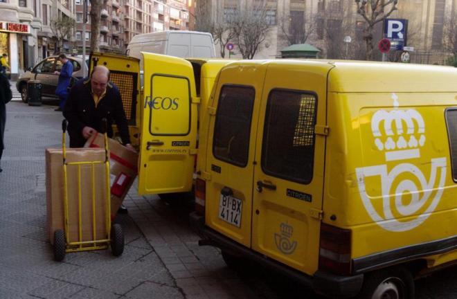 Un trabajador de Correos introduce en una de las furgonetas de reparto...