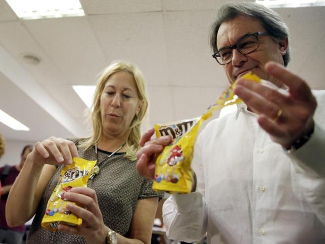 Neus Munté y Artur Mas abren unas bolsas de caramelos haciendo una...