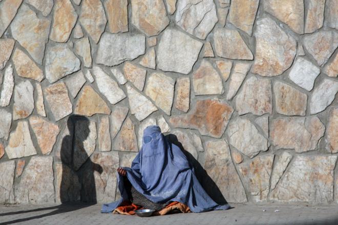 Mujer afgana  sentada contra un muro.