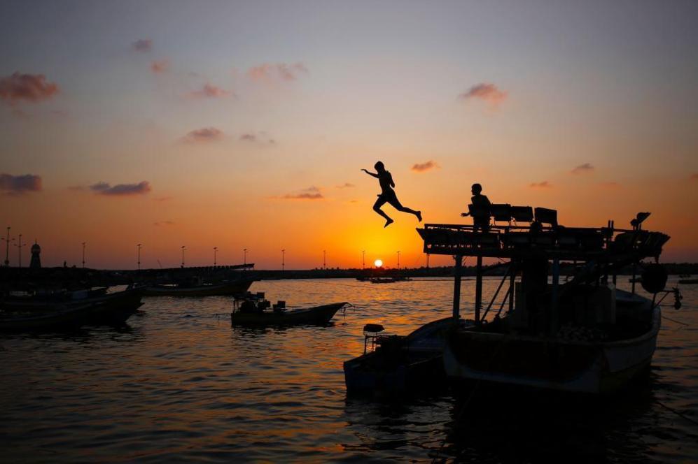 Un chico salta al mar en pleno atardecer en la ciudad de Gaza.