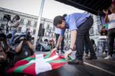 Pablo Iglesias despliega una ikurriña en el escenario durante un...