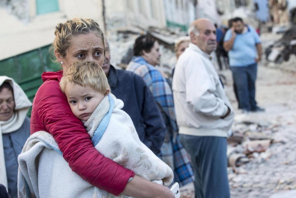 Una mujer abraza a su hijo en medio de los escombros en Amatrice.