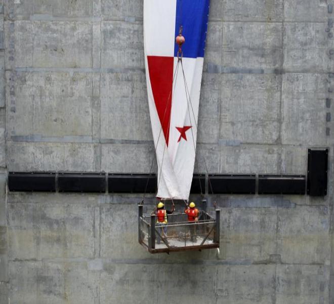 Trabajadores despliegan la bandera de Panamá sobre una de las...