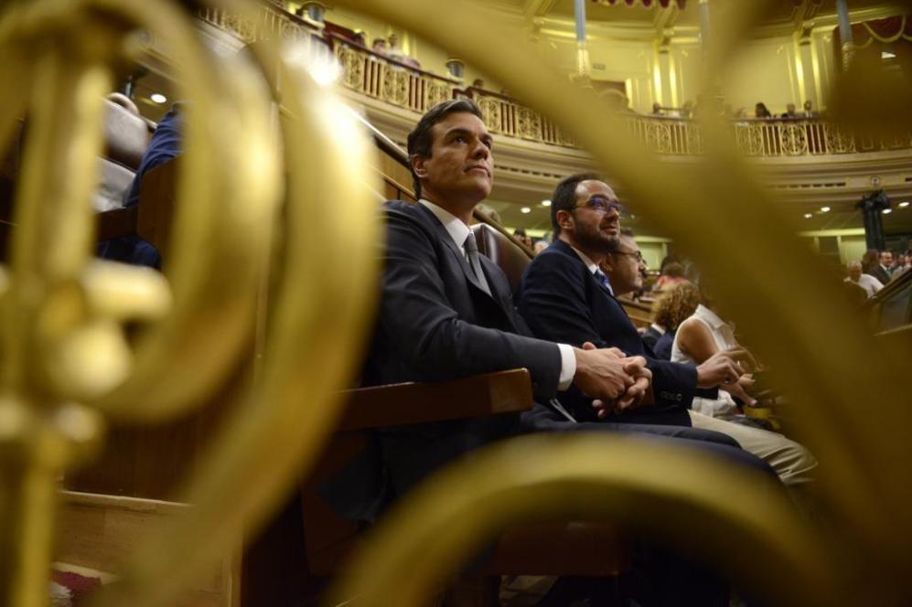 El líder del PSOE, Pedro Sánchez (i), sentado en su escaño junto al...