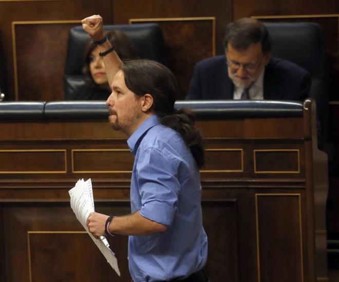 Pablo Iglesias pasa delante de Mariano Rajoy durante el debate de...