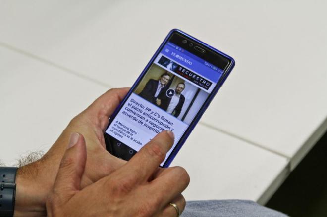 Un usuario lee EL MUNDO en su aplicación para móviles.