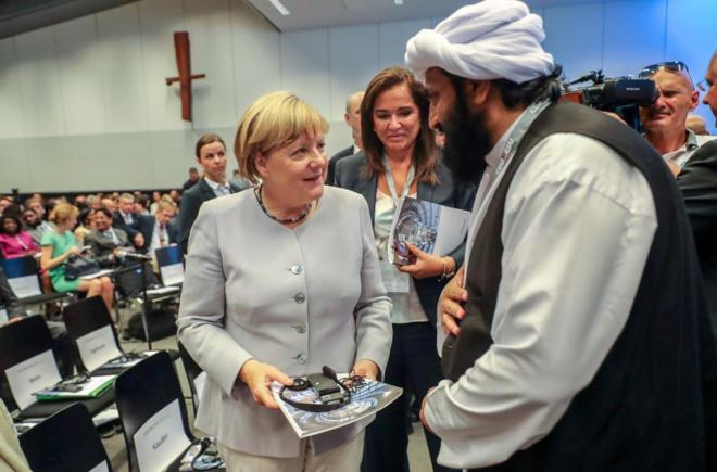 La canciller alemana, Angela Merkel, conversa con un refugiado en...