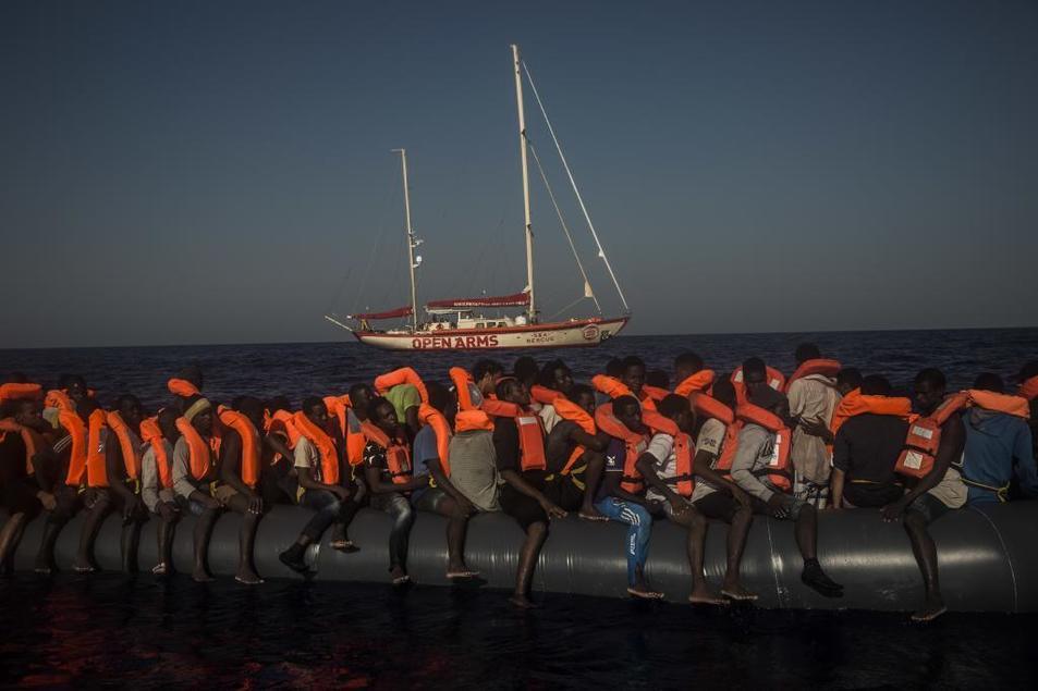 Una embarcación sobrecargada con refugiados apoyados en las gomas...