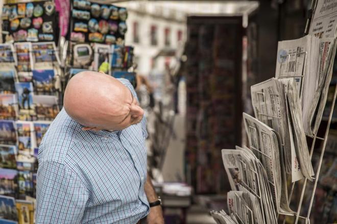 Un lector mira las portadas de los periódicos en un quiosco.