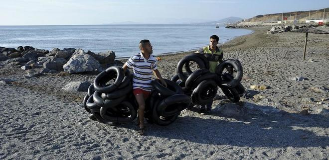 Dos personas con flotadores que utilizaron los inmigrantes para entrar en la playa ceutí de El Tarajal.