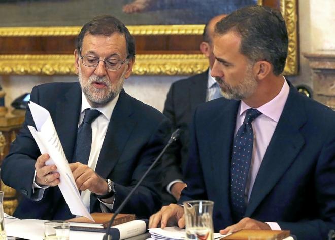 Mariano Rajoy enseña un documento al Rey Felipe VI el martes, durante...