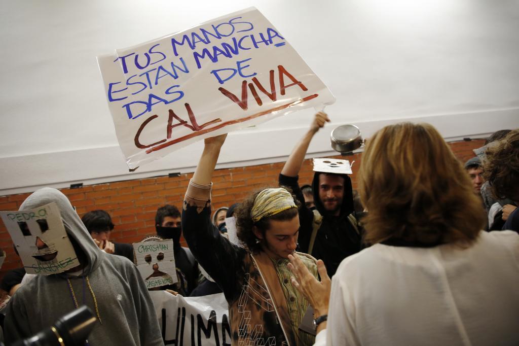 """Uno de los manifestantes que impidió el acto de González porta la pancarta con el mensaje """"Tus manos están manchadas de cal viva""""."""