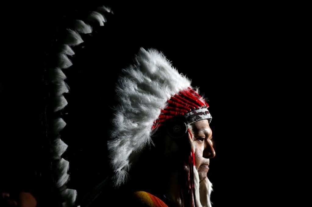 Perfil de un hombre indígena ataviado con un tocado nativo durante un...