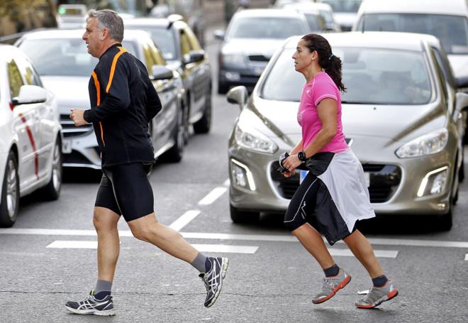 Dos corredores cruzan por una céntrica calle madrileña.